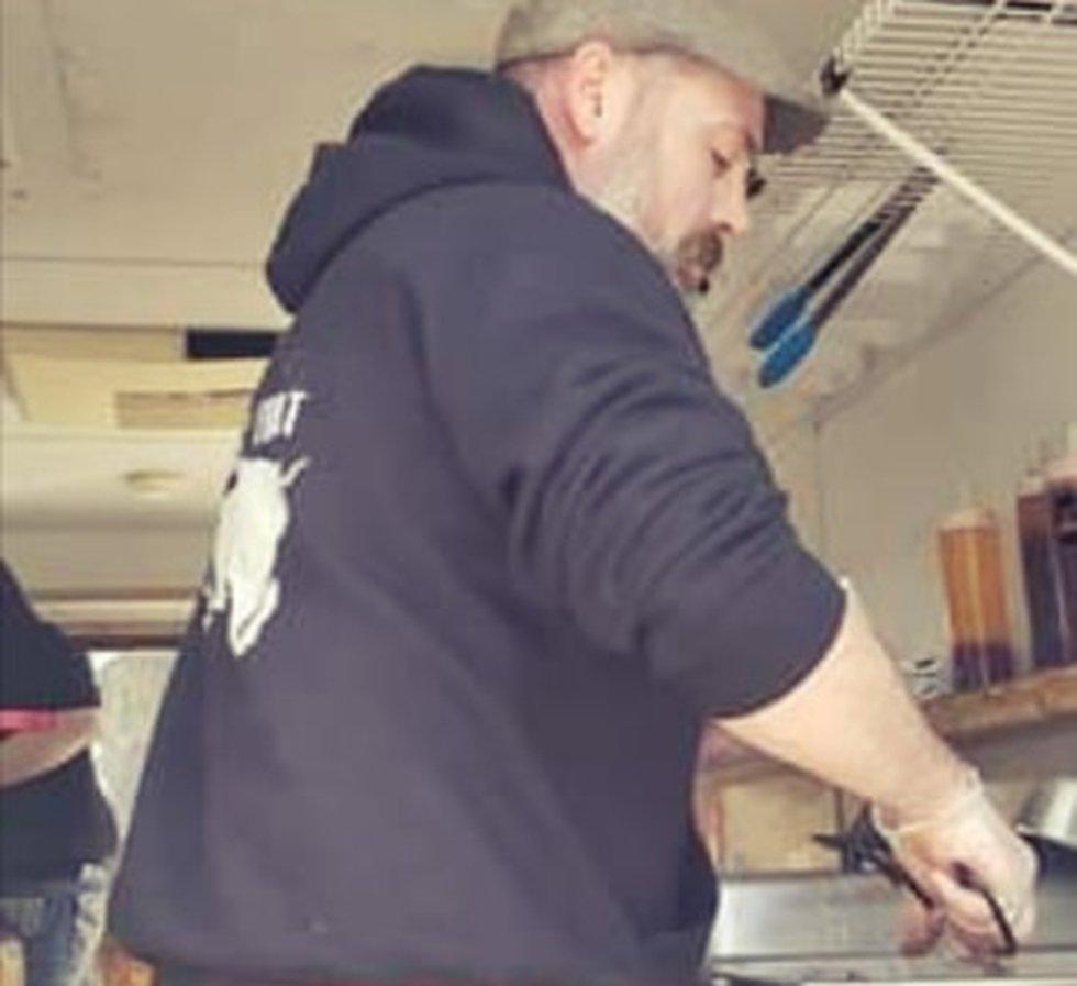 Chef Jason Olszewski of OL'Chefskis food truck prepares food during social distancing